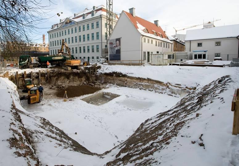Mit Schnee bedeckte Baustelle, im Hintergrund Baufahrzeuge und weiße Gebäude