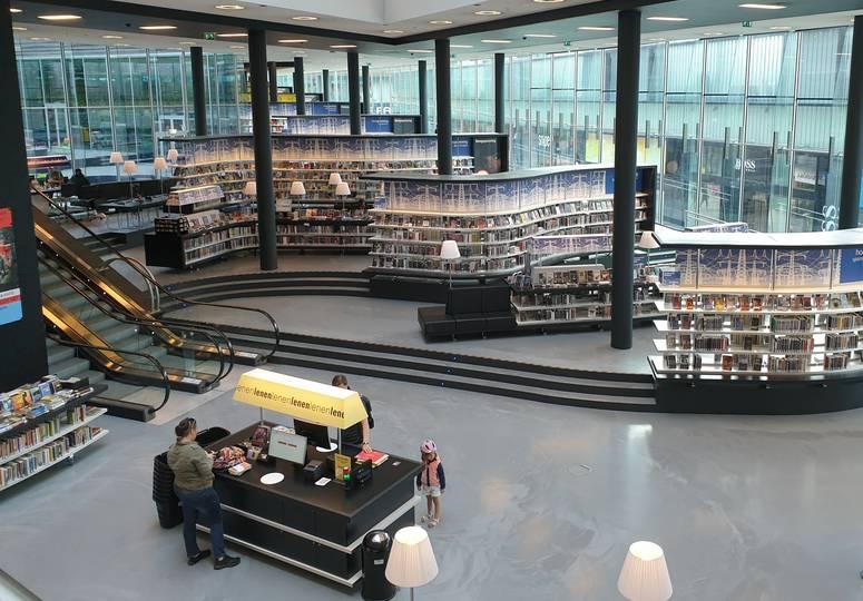 Saal mit Glasfassade, vielen Bücherregalen und Empfang
