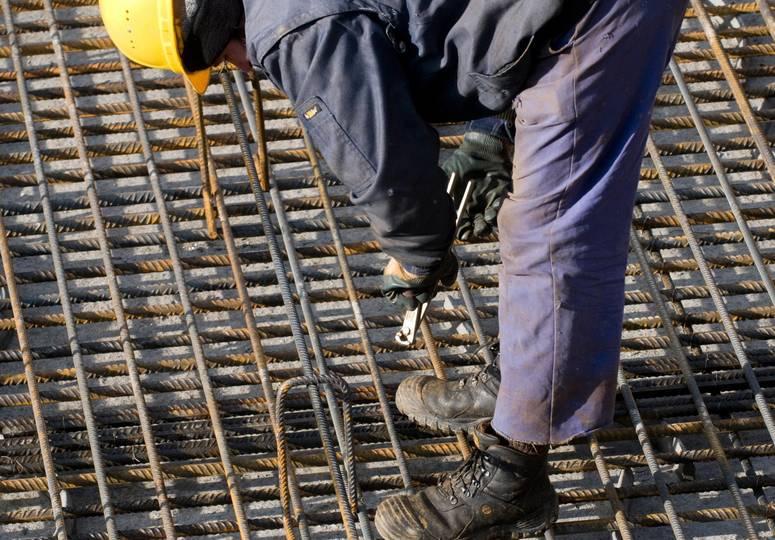Ein über eine Stahlkonstruktion gebeugter Bauarbeiter