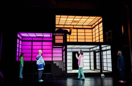 Bühneninstallation mit bunt belauchteten Räumen und fünf Personen