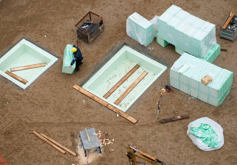 Vogelperspektive auf einen Bauarbeiter, der mit von Planen bedeckten Holzpaletten beschäftigt ist