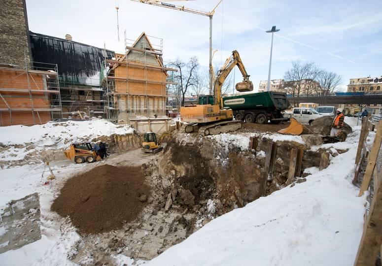 Mit Schnee bedeckte Baustelle, im Hintergrund ein Schaufelbagger