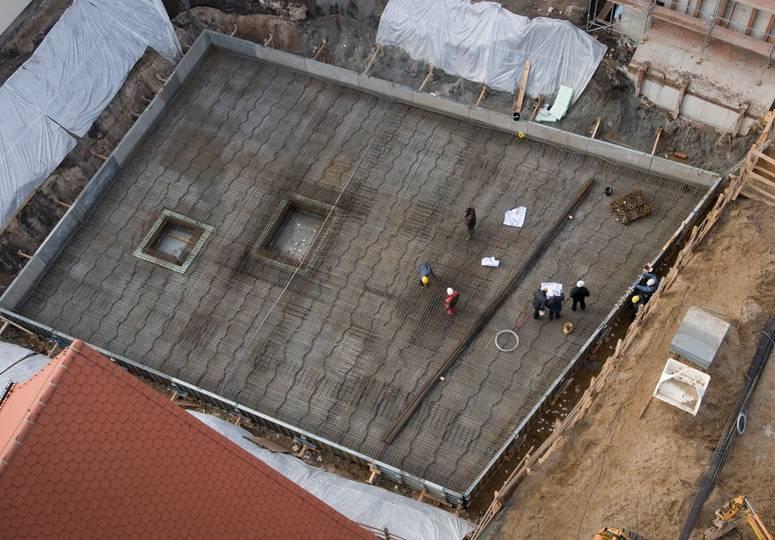 Vogelperspektive auf ein Baustellenfundament mit mehreren Bauarbeitern darauf