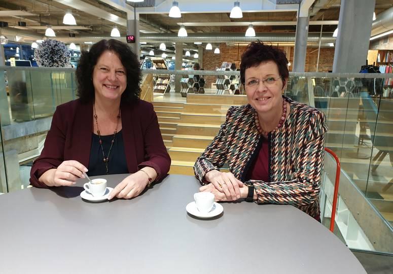 Zwei Frauen am Cafétisch in Saal lächeln in die Kamera