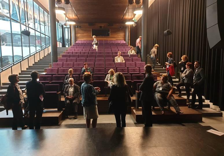 Personengruppe in einer Art Hörsaal mit rot gepolsterten Sitzreihen