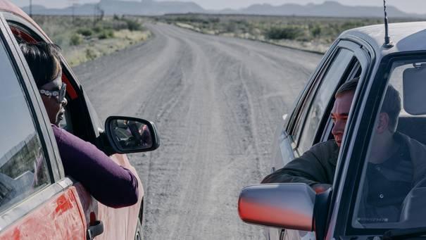 Zwei Personen schauen einander aus heruntergelassenen Autofenstern an