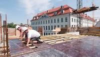 Zwei kniende Bauarbeiter sind mit Bodenplatten beschäftigt