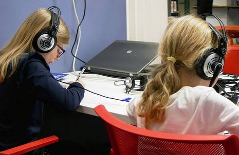 Zwei Mädchen mit Kopfhörern sitzen an einem Arbeitstisch