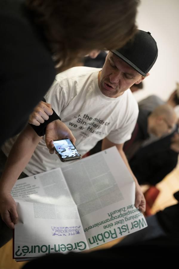 Ein Mann hält eine aufgeschlagene Zeitschrift und blickt auf ein Handy, das ihm hingehalten wird