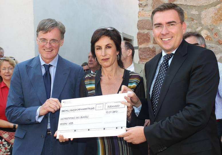 Zwei Männer und eine Frau halten zusammen einen großen Scheck in den Händen