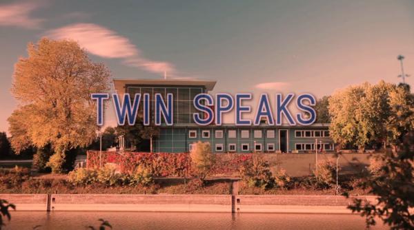 """Im Vordergrund Schriftzug """"Twin Peaks"""", im Hintergrund von Bäumen umgebenes Gebäude"""