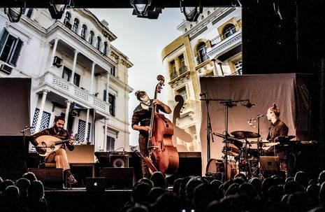 Bühne mit drei Musikern, ein großer Bildschirm dahinter zeigt zwei Gebäude