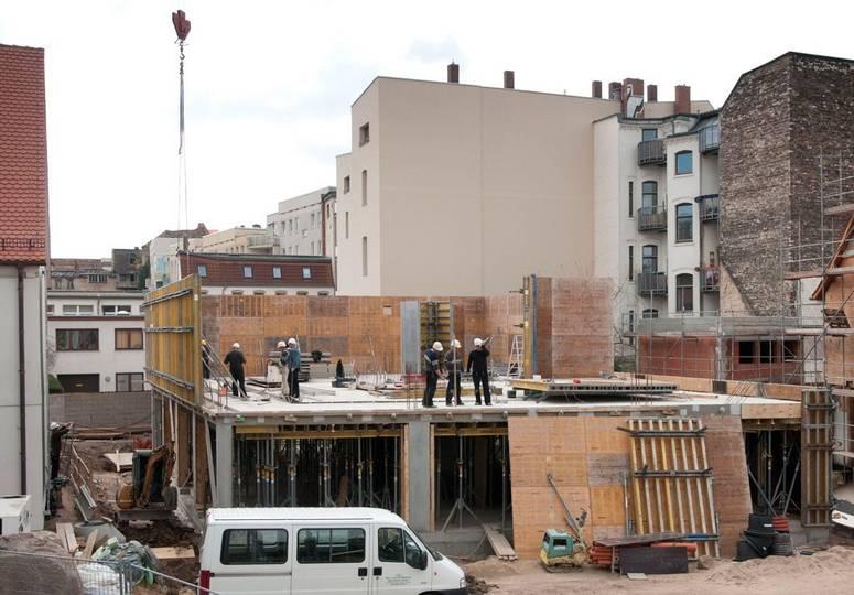 Blick auf sich im Bau befindendes zweites Obergeschoss mit mehreren Bauarbeitern