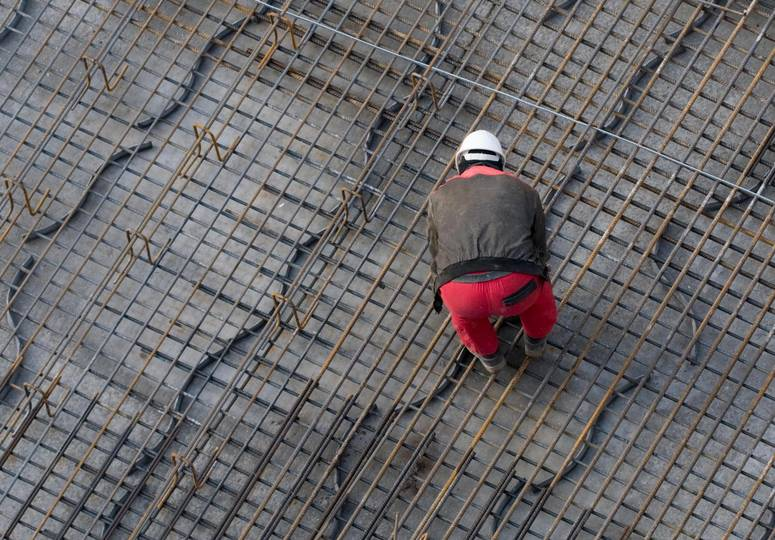 Vogelperspektive auf Bauarbeiter auf mit Stahl bedecktem Baufundament