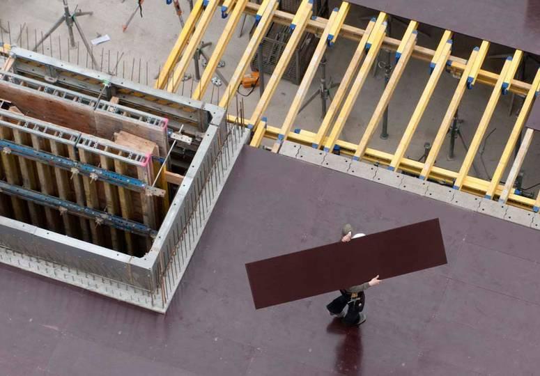 Vogelperspektive auf einen Bauarbeiter, der eine Platte über dem Kopf trägt