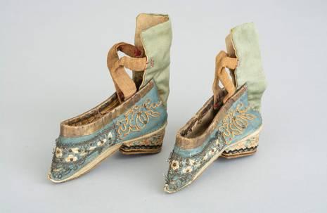 Ein Paar kleiner mit chinesischem Blumenmuster bestickter Schuhe auf weißem Grund
