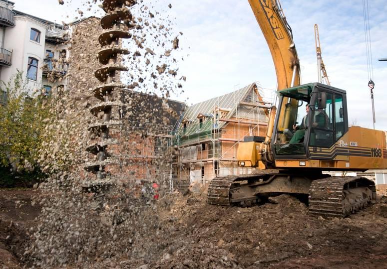 Ein Baufahrzeug zieht einen großen Bohrer aus dem Boden, Schlamm spritzt auf