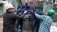 Zwei Männer mit Helm stabilisieren mit den Händen eine Baukonstruktion