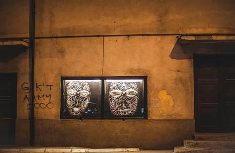 Zwei mit weißen Ornamenten gestaltete Gesichter blicken aus schwarzem Schaukasten in einer Gebäudewand