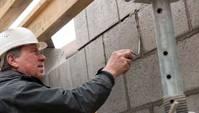 Nahaufnahme eines Bauarbeiters beim Spachteln einer Mauer