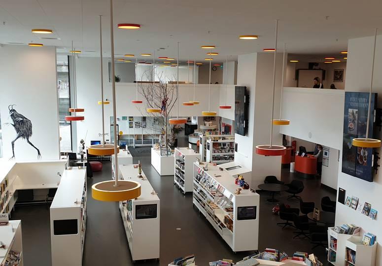 Blick in weiß gestalteten Saal mit Bücherregalen und zwei Ebenen