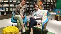Zwei Frauen in Sesseln lächeln in die Kamera, im Hintergrund Bücherregale