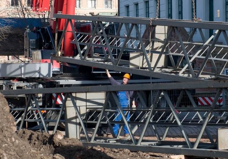 Ein Bauarbeiter umgeben von Stahlträgern