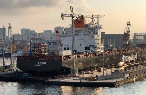 """Hafen mit sich im Bau befindenden Schiff mit der Aufschrift """"Hapag-Lloyd"""""""