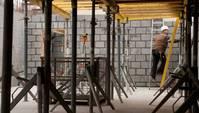 Bauarbeiter auf einer Leiter im Rohbau eines Gebäudes