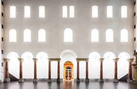 Palastartiger Saal mit vielen Fenstern, roten Säulen und einer zentralen bunten Tür