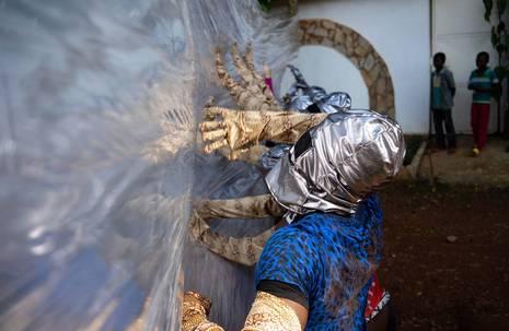 Personen mit silberner Kopfbedeckung und armlangen Handschuhen betasten eine mauerhohe Folie