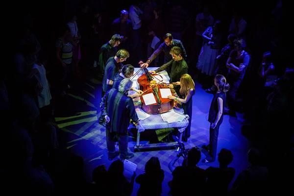 Das Ensemble MCME, Teil des Ensemblefestival für aktuelle Musik, bei einem Auftritt: 7 Menschen stehen rund um einen Tisch mit einem darauf liegenden Cello und begutachten es neugierig