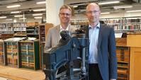 Zwei Männer in einer historischen Bibliothek lächeln in die Kamera