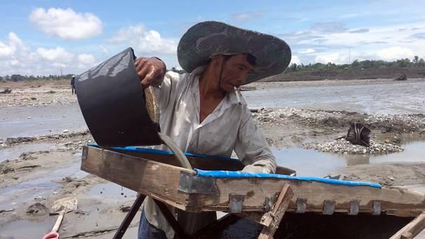 Mann mit breitkrempigem Hut gießt Schlamm aus einem Eimer in eine Holzvorrichtung