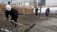 Drei Bauarbeiter sind mit Handwerkzeugen und Schläuchen am Baufundament beschäftigt