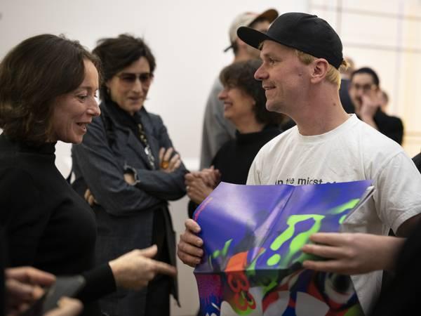 Ein Mann hält ein Plakat in den Händen, auf das eine Frau blickt. Im Hintergrund weitere Personen.
