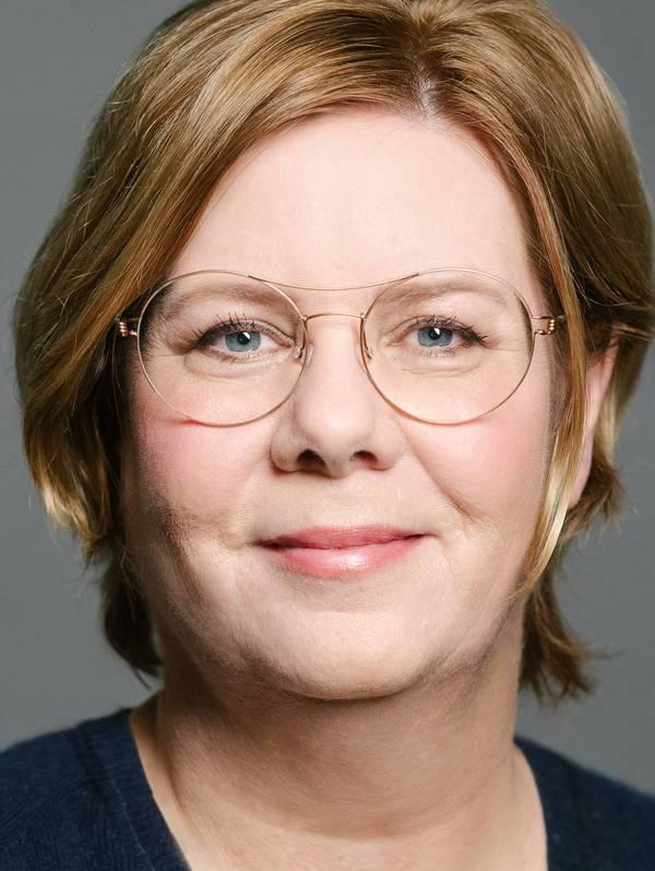 Lächelnde Frau mit kurzen hellen Haaren und Brille