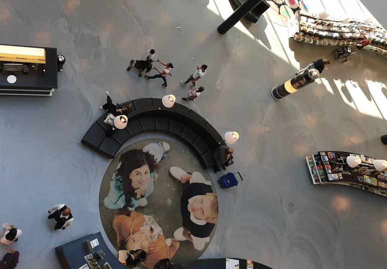 Vogelperspektive auf Saal mit rundem Teppich, darauf drei hochblickende Perseonen