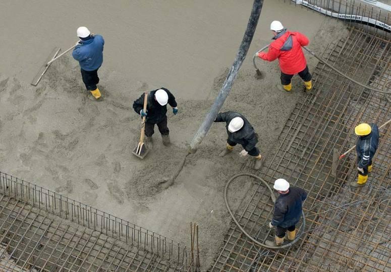 Vogelperspektive auf sechs Bauarbeiter, die am Baufundament arbeiten