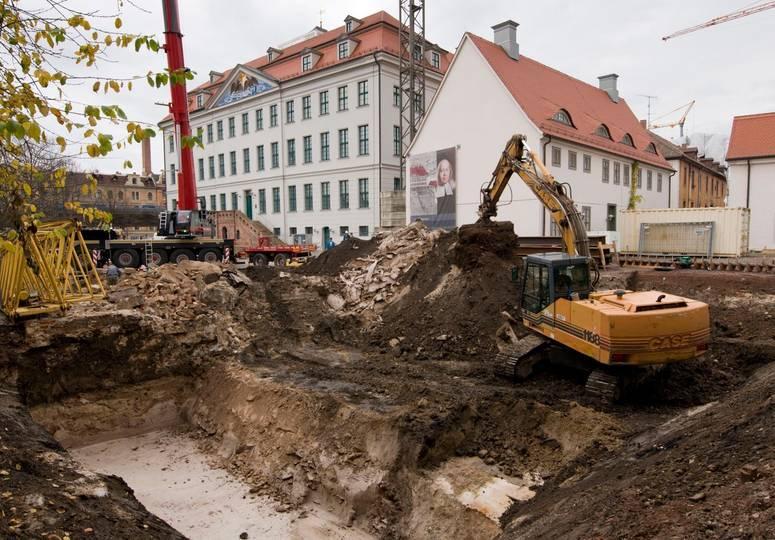 Baustelle mit großen Erdhügeln und einem Schaufelbagger, im Hintergrund weiße Gebäude