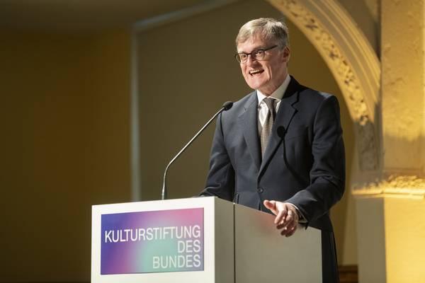 """Ein Mann am Rednerpult mit Aufschrift """"Kulturstiftung des Bundes"""""""