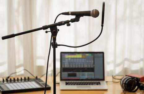 Im Vordergrund ein Mikrofon an einem Ständer, im Hintergrund Kopfhörer und ein Laptop mit geöffnetem Programm zum Musikschnitt