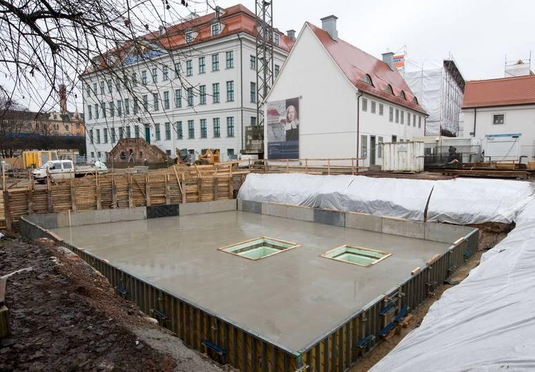 Baugrube mit glänzendem Betonfundament