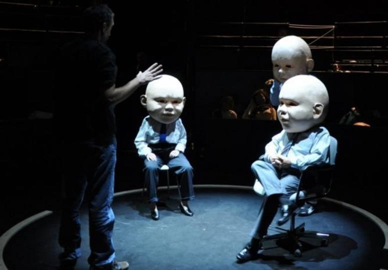 Mann steht gestikulierend vor drei Personen in Anzügen mit riesigen Puppenköpfen
