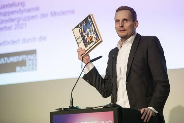 Mann am Rednerpult hält Buch in die Höhe