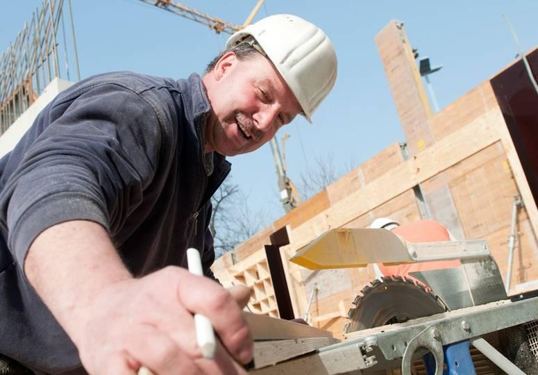 Lachender Bauarbeiter an einer Kreissäge