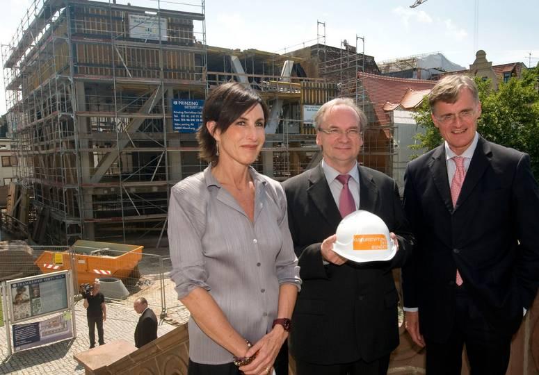 Eine Frau und zwei Männer, einer davon mit Helm in der Hand, posieren vor dem Rohbau eines Gebäudes