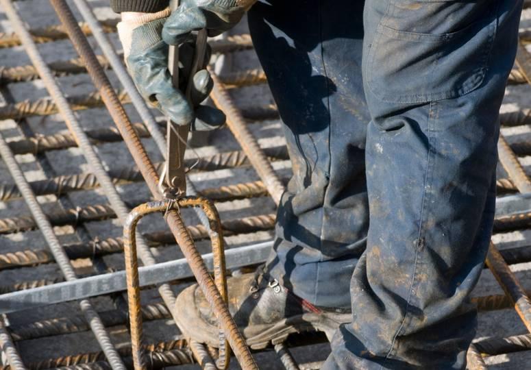 Beine und Hände eines Bauarbeiters, der an einer Stahlkonstruktion arbeitet