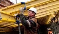 Ein Bauarbeiter arbeitet an gelben Stahlträgern