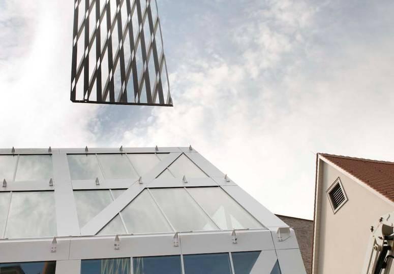 Ein Rechteck weiß gemusterter Außenverkleidung hängt an einem Seil über den Fenstern eines Gebäudes